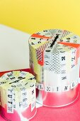 Empty paint tins decorated with washi tape and with slots in top used as money boxes