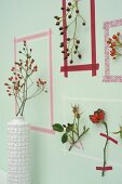 Picture frames made from washi tape around sprigs of rose hips on wall