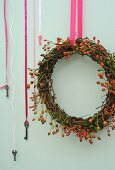 Willow and rose hip wreath hanging from pink ribbon