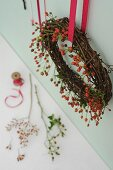 Willow and rose hip wreath hanging from red ribbon