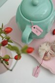 Turquoise teapot of rose hip tea and sprig of rose hips in vintage ambiance