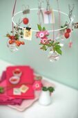 Sprigs of rose hips and delicate wild roses in tiny glass bottles hanging from white metal wreath