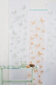 Wallpaper decorated with stencilled butterflies