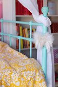 Detail of turquoise, lattice metal bed with white and yellow patterned bed linen