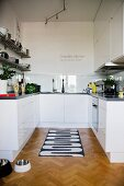 Black and white patterned rug on herringbone parquet floor in open-plan, white designer kitchen