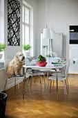 Dog sitting on white shell chair with metal frame at set table in modern dining room with traditional atmosphere