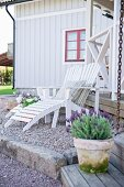 White wooden lounger on gravel terrace outside wooden house with red window