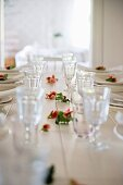 Set, white dining table with roses strewn amongst glasses