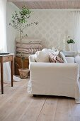 Sofa with white loose cover, small potted olive tree and stack of cushions in rustic living room with wooden floor