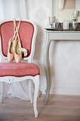 Ballet shoes on Rococo-style chair with pink velvet cover next to console table with curved legs