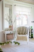 White fur blanket on wicker chair and console table below framed mirror in rustic living room