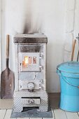 Old wood-burning stove next to blue metal bucket with lid in rustic interior