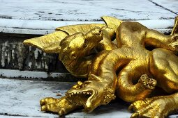 A gilded dragon statue on a stone floor in the Garden of the Palace of Versailles