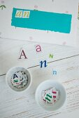 Hand-crafting envelopes - paper letters on wooden surface and sorted in white china dishes