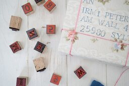 Wrapped gifts with old-fashioned, hand-crafted address labels and black alphabet and number stamps on white, vintage wooden surface