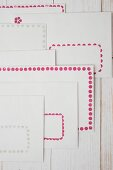 Stamped borders of dots in pink and pale grey on white envelopes