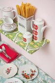 Crockery and china pot of pasta on shelf covered in oil cloth on pink wall