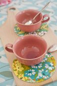Pink cups on patterned coasters made from oilcloth remnants