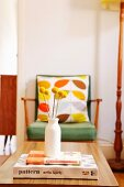 Simple vase of dried yellow flowers on stacked books and coffee table; 50s armchair with patterned scatter cushions in background