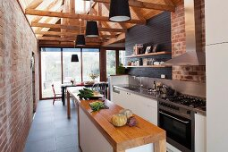 Open-plan kitchen in renovated brick house with black pendant lamps suspended from exposed wooden roof structure