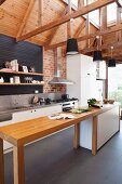 Narrow wooden counter with base units in open-plan, white designer kitchen with pendant lamps suspended from exposed wooden roof structure in modern country house