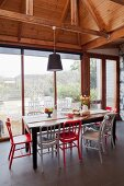 Red and white chairs around rustic wooden table next to glass wall and below exposed wooden roof structure