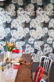 Vase of flowers on wooden table in front of wall covered in floral wallpaper