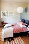 Double bed with red and white striped bed linen against partition and white wooden wall in background in rustic, modern bedroom