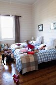 White and blue gingham bed linen on twin beds in rustic children's bedroom with white, wood-clad walls; children playing with dog