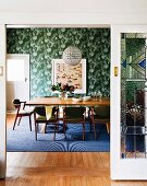 View through open sliding door into dining room with upholstered chairs around table and green wallpaper with white floral pattern
