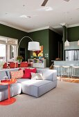 Couch, arc lamp, kitchen counter and dining area against dark green walls