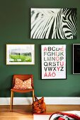 Various posters on dark green wall above leather chair and handbag on floor