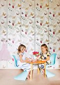 Little girls sitting on pale blue chairs at round table in front of fitted cupboards covered in butterfly-patterned wallpaper