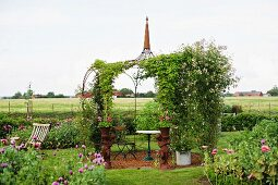 Romantic seating area under climbing roses on delicate metal pavilion in rural setting
