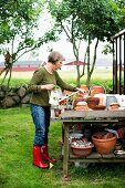 Woman gardening - various terracotta pots on wooden table with shelf in garden