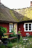 Corner of idyllic courtyard with vintage table and chairs enclosed by Swedish wooden house with thatched roof