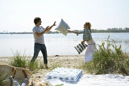Couple on a beach picnic throwing cushions