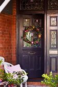 Wreath of flowers on dark grey front door with stained glass windows