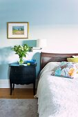 Bouquet on black, antique bedside cabinet next to double bed