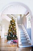 View through arched, open doorway of decorated Christmas tree next to white, wooden staircase in foyer