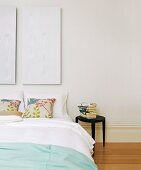 White diptych above double bed with floral scatter cushions next to stack of books on stool used as bedside table