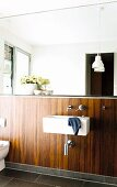 Sink and toilet against half-height wall panelled in exotic wood