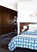 Bed room with blue and white bed linen; corridor with fitted wardrobes in dark wood to one side