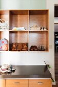 Shoes, bags and sporting equipment in square shelf compartments above chest of drawers