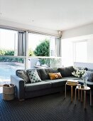 Grey corner sofa in front of glass wall with half-height folding windows and view of pool; Scandinavian stools used as side tables