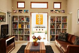 Living room with leather couch and wooden table; view of decorative, yellow artwork through open terrace door flanked by bookcases