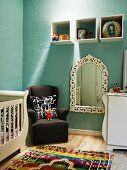 Elegant cot and changing unit in nursery painted pastel blue; ornaments in wall mounted shelving units above period armchair and ornate mirror on wall