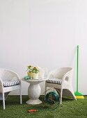 White wicker garden furniture, various gardening utensils and devices on artificial lawn