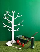 White, stylised wooden tree, flowers in wheelbarrow and gardening utensils on artificial lawn against green wall