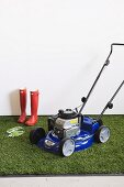 Lawn-mower and gardening equipment on artificial lawn against white wall